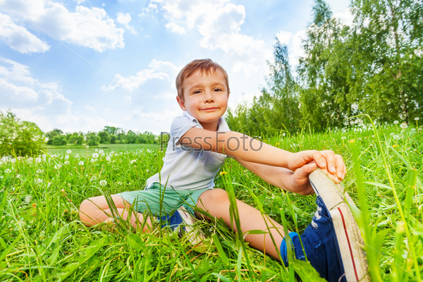 Boy sit on a grass and does gymnastics
