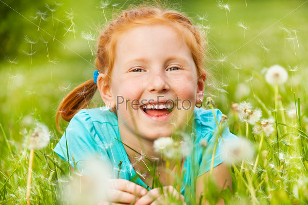 Nice little girl smiles laying on a grass