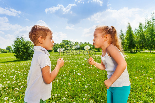 Two kids blow dandelions