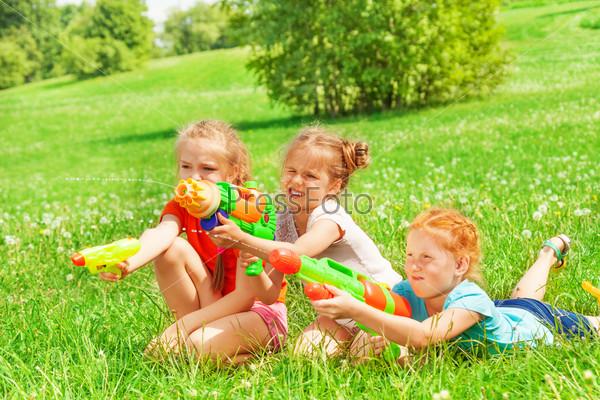 Three beautiful girls playing on a grass