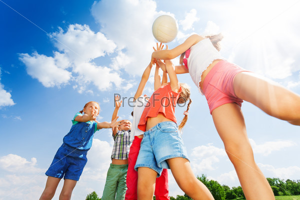 Group of children plays ball on a meadow