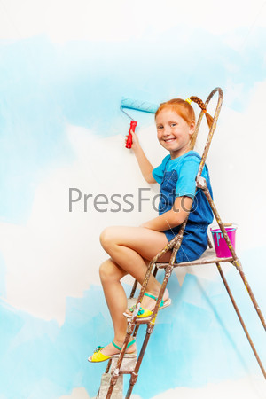 Nice little girl in blue sits on a ledge