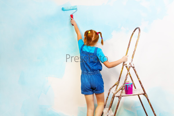 Little girl in blue paints the wall on a ladder