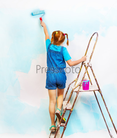 Little girl in bib and brace stands on a ladder