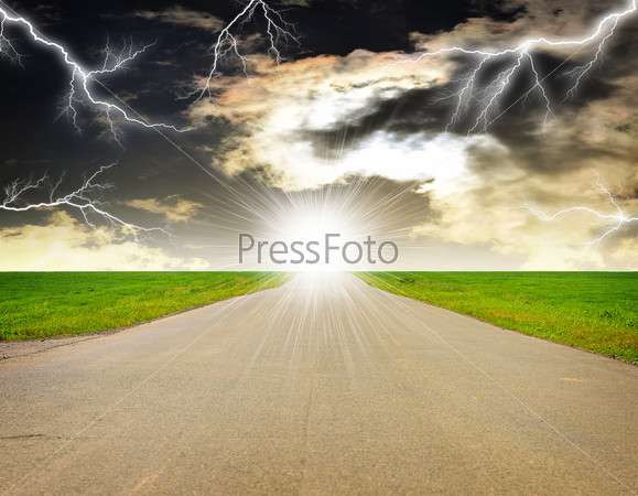 Old road, roadsides and green grass field. Stormy sky with lightning in background