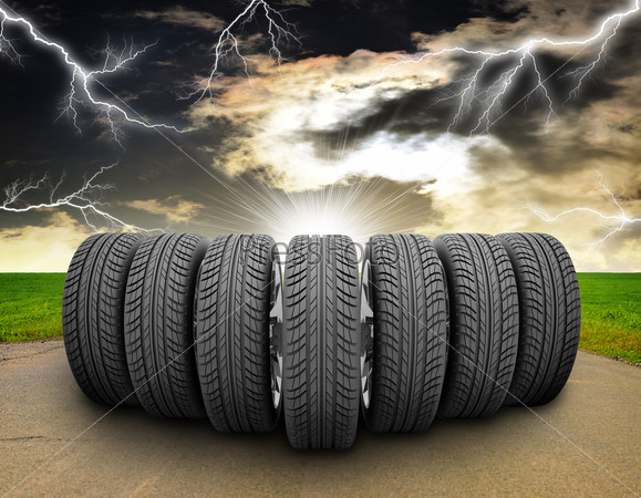 Wedge of car wheels. Road, roadsides, grass field and stormy sky in background