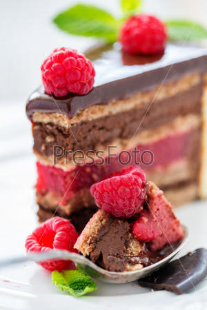 Spoon with chocolate cake and raspberries.