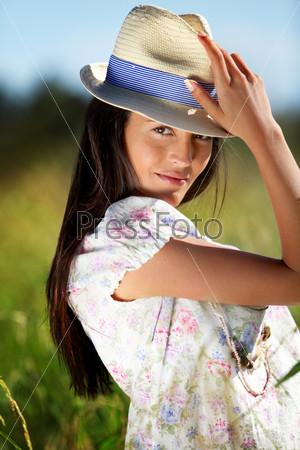 Цыганка с шляпе стоит в поле диких цветов