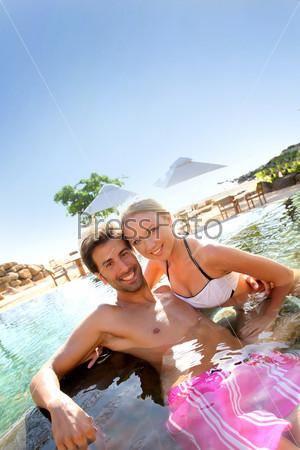 Пара, отдыхает в бассейне