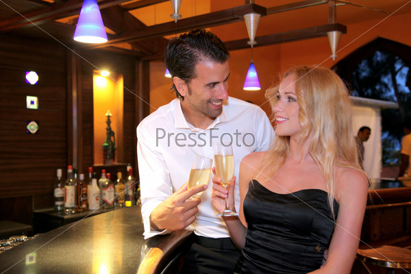 Пара, выпивает шампанское в модном баре