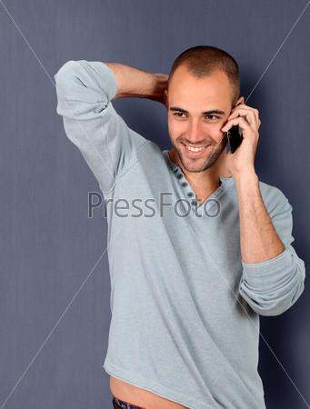 Молодой человек, опирается на голубую стену и разговаривает по мобильному телефону