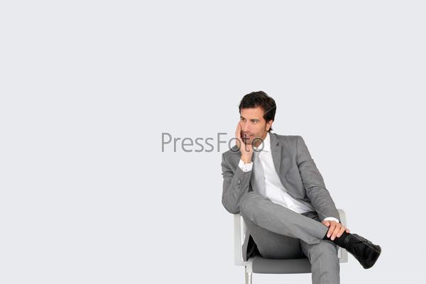 Бизнесмен, сидит на стуле на сером фоне