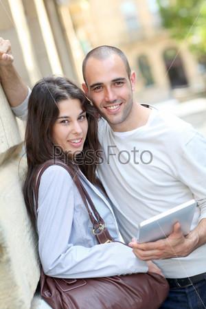Молодая пара в городе с планшетом