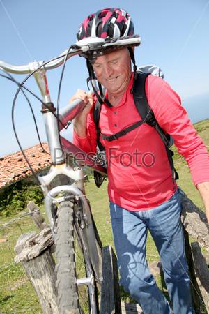 Взрослый мужчина с горным велосипедом