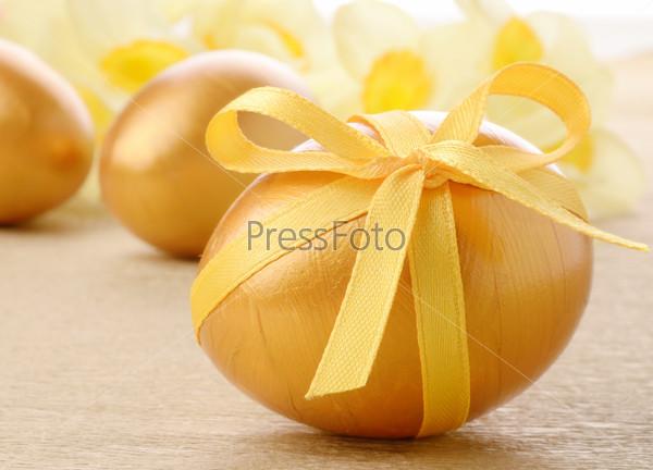 Пасхальные яйца с бантиками на золотом фоне