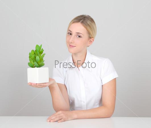 Красивая блондинка, держащая растение в горшке