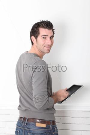 Мужчина опирается на стену с Электронным планшетом