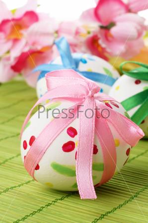 Пасхальные яйца с бантиками на зеленом фоне