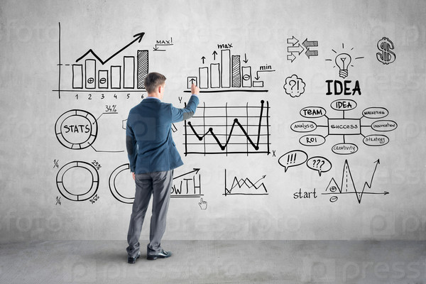 businessman drawing  business plan, graph, chart on wall