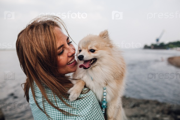 Young woman is holding dog outdoors