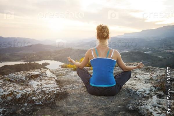 Молодая женщина занимается йогой на холме