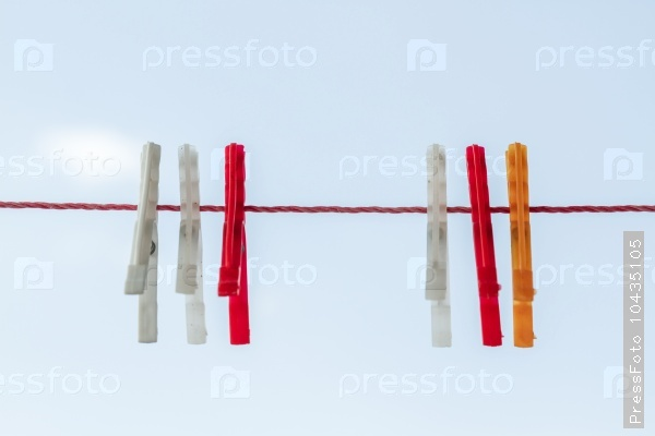 White, Red, Orange Cloth Pins Hanging on Red Rope