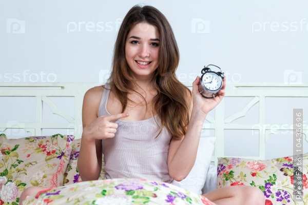 The young girl in bed with  clock service
