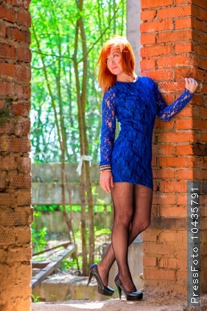 charming woman in a dress and stockings near the brick wall