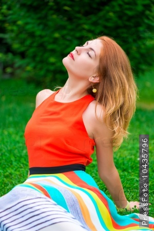 Bright woman relaxing on the lawn in the park