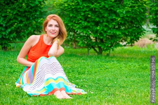 woman in a dress sits on a green lawn
