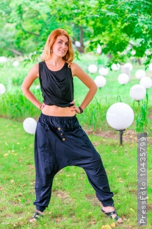 slim fashionable woman in black clothes in the park