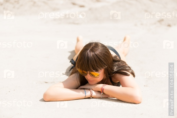 Brunette in bathing suit basking in the hot sand on the beach