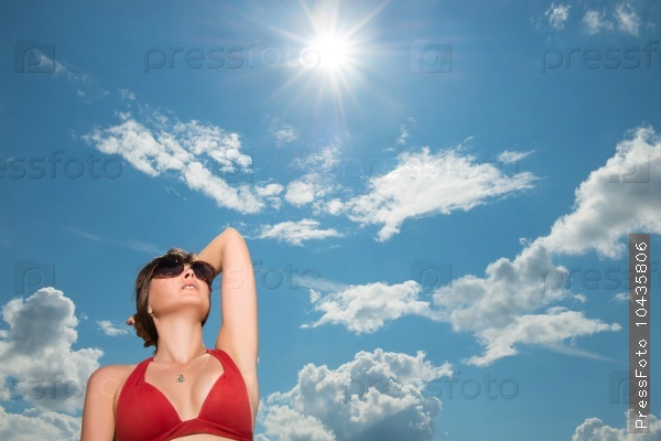 woman on the background of the sun and the sky in a bikini
