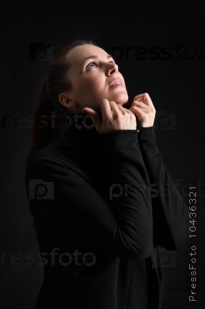 brunette woman looking up in darkness. praying