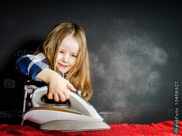 cute little girl helping your mother by ironing clothes