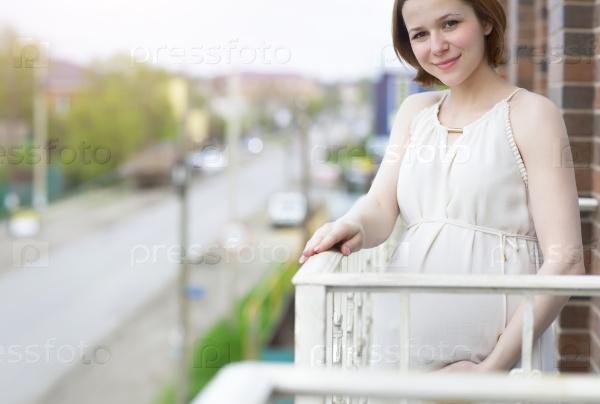 Красивая беременная женщина на балконе