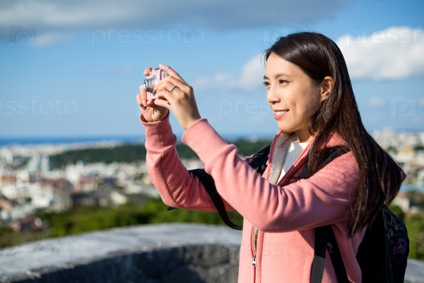 Девушка фотографирует город