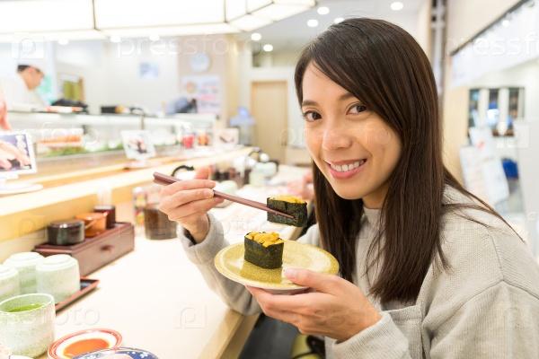 Девушка кушает суши