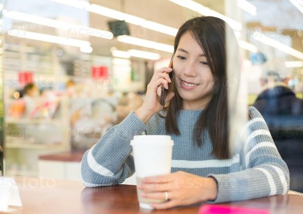 Девушка разговаривает по телефону в кафе