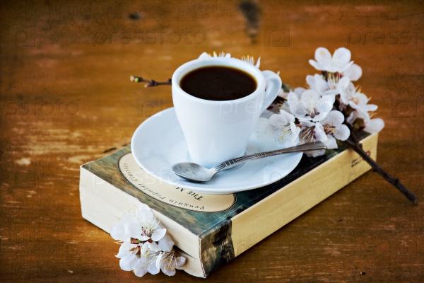 Чашка кофе, книга и цветущая ветка