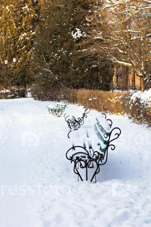 Скамейка в снегу в парке