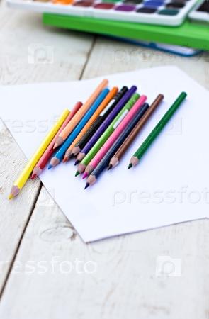 Цветные карандаши и бумага на столе
