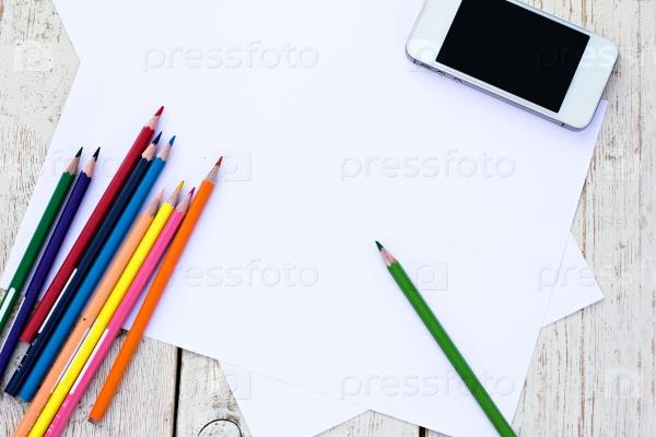 Цветные карандаши, сотовый телефон и бумага на столе