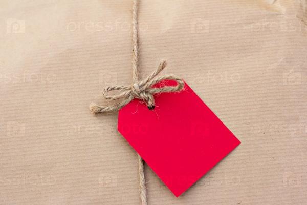 Подарок в крафт-бумаге с красным тегом