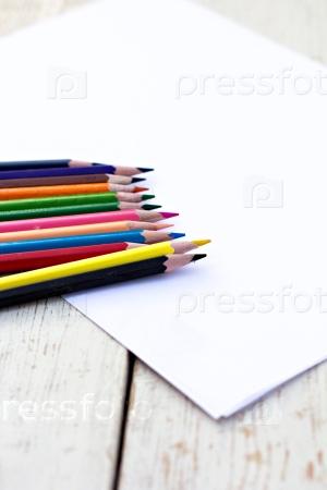 Цветные карандаши и лист бумаги на столе