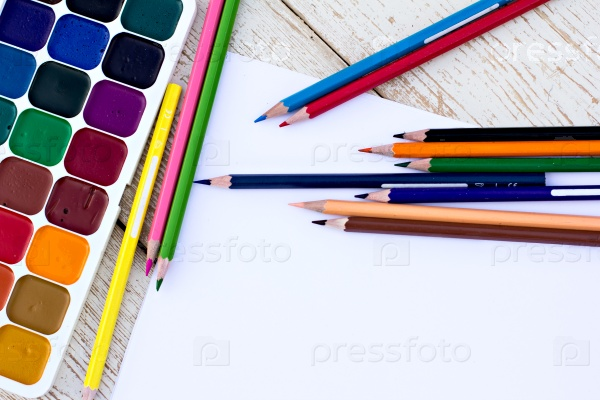Цветные карандаши, акварель и бумага на столе