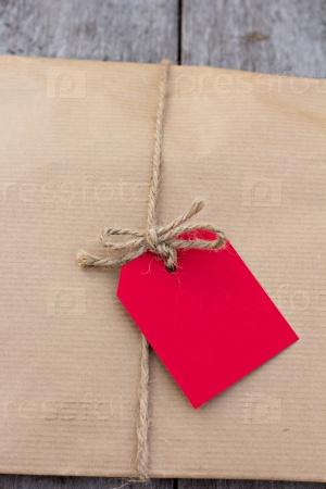Подарок в крафт-бумаге с красной карточкой