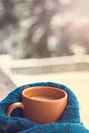Чашка с горячим напитком на фоне зимнего леса