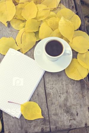 Чашка кофе эспрессо и блокнот на фоне осени