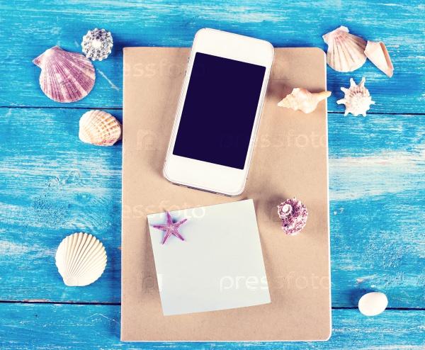 Раковины, блокнот и мобильный телефон